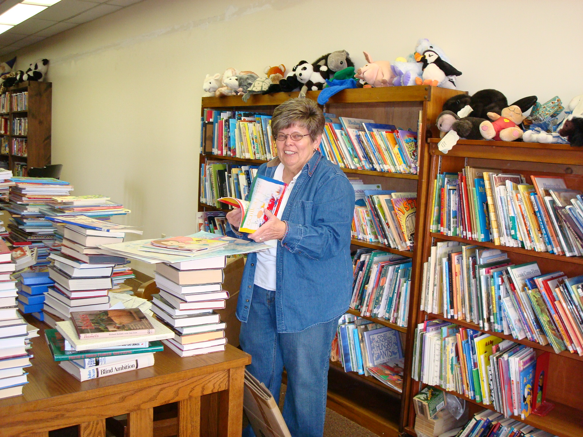 Margaret Scott sorting through the children's book section