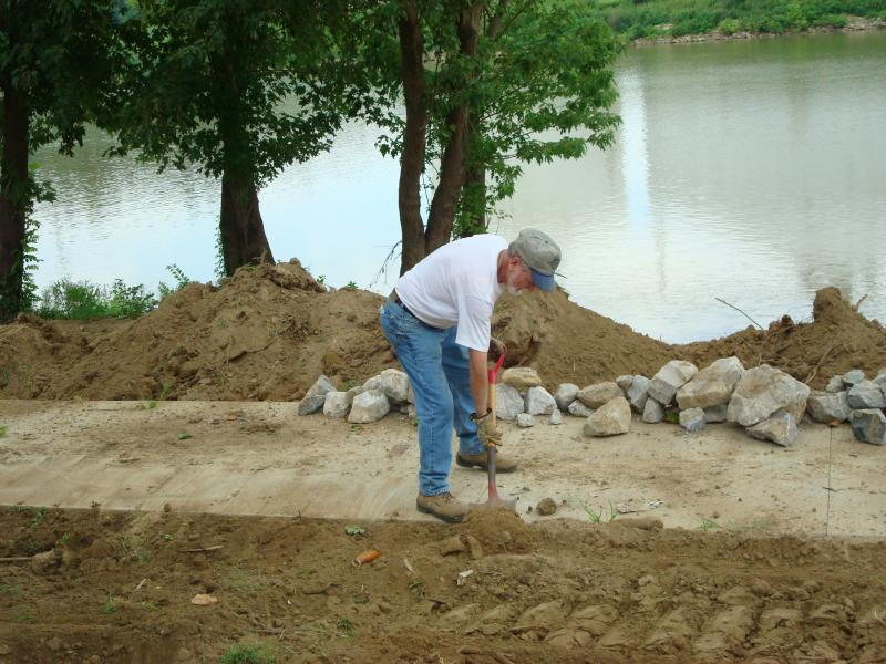 Sonny Renfrow shoveling the sand off the riverwalk