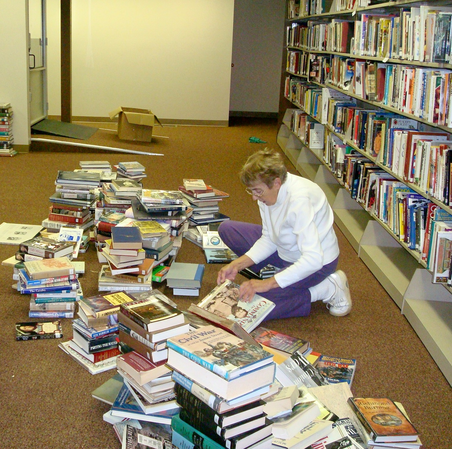 Mrs. Doris Turner sorting thru  library books preparing for reopening of library